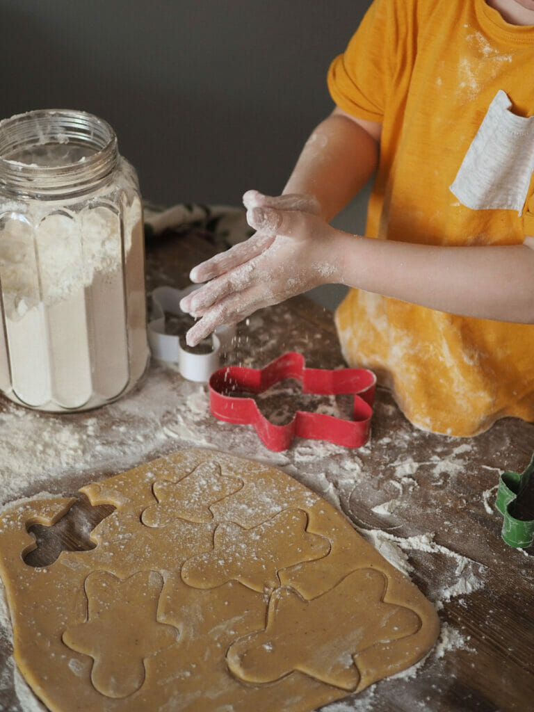 hands rubbing flour together over rolled out gingerbread cookies